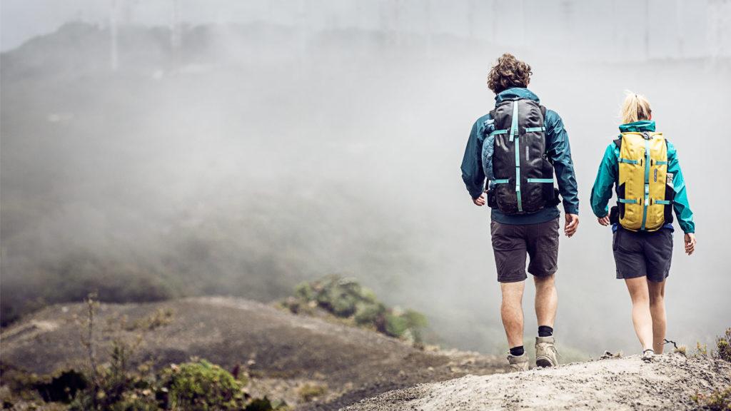 Twee mensen lopen met een waterdichte rugzak in de bergen